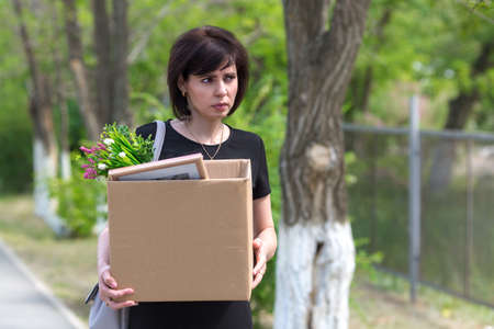 A frustrated fired woman with a box in her hands walks through the city.
