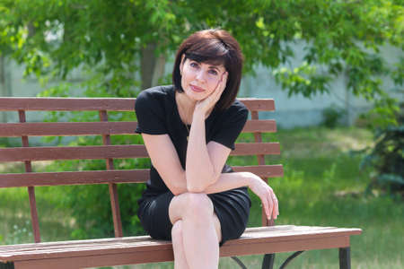 Portrait of a happy young woman in black dress on a bench in the park. Banque d'images