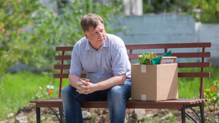 A frustrated man sits on a bench with a box in the park after being fired. Banque d'images