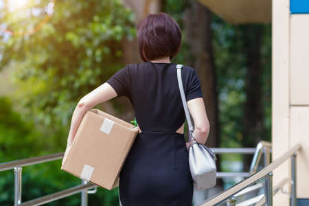 Brunette with a chic figure with a box of personal items, rear view.