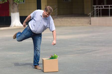 Enraged man kicks box of personal belongings after being fired.