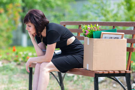 A frustrated fired woman in a black dress with a box sits on a bench in a park.