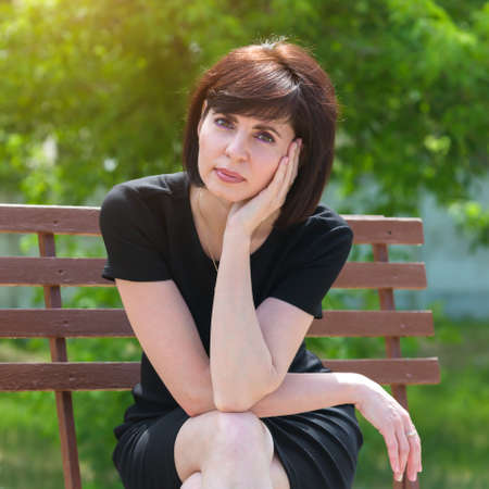 Portrait of a happy young woman in a black dress on a bench in the park.