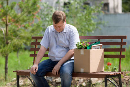 A frustrated man sits on a bench with a box in park after being fired.
