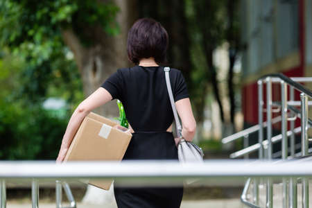 Brunette with a chic figure with a box of personal items rear view.