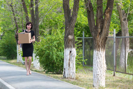 A frustrated fired woman with box in her hands walks through the city.