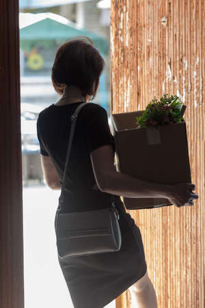 An outraged woman with a box in her hand after being fired opens door with her foot.
