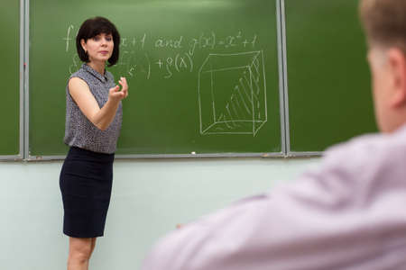 The teacher stands at the blackboard and asks student to answer with a hand gesture.