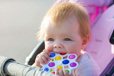 A child sits in a pram with a bright toy in his hands.