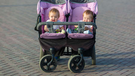Father drives a baby carriage with two twin daughters.