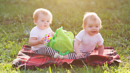 Twin sisters sit on a blanket with a backpack of children's toys. Banque d'images