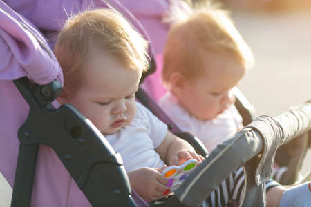 Twin children sit in baby carriage with toys in their hands. Banque d'images