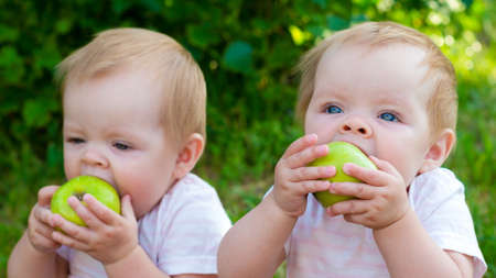 Twin girls eat apples in nature in the fresh air.