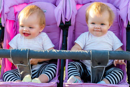 Two beautiful little twin babies, portrait in a baby carriage. Banque d'images