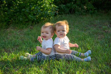 Two twins sit with their backs leaning on green grass in a city park.