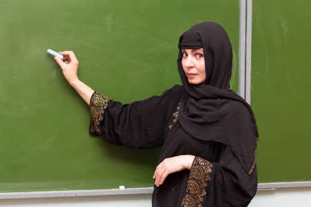 A Muslim teacher writes with chalk on blackboard. Banque d'images