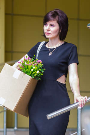 A woman after being fired goes down stairs with a box of personal belongings.