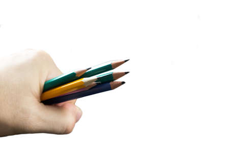 A bunch of colored pencils in a man's hand on a white background isolated.