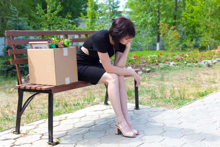 A frustrated fired woman in black dress with a box sits on a bench in a park.