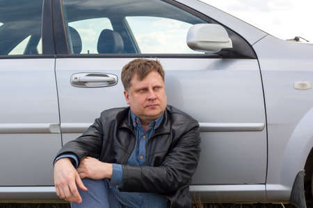 A tired driver sits on the grass near the car in the steppe. Banque d'images