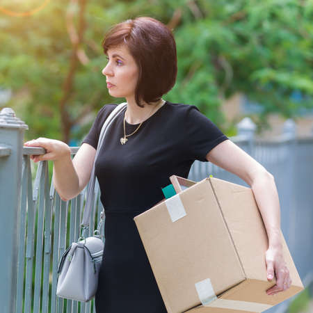 A fired woman with box of personal belongings stands at the fence thinking. Banque d'images