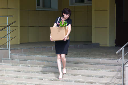 A woman after being fired goes down the stairs with a box of personal belongings.