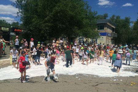 Orenburg, Russia - June 18, 2021, Children play in foam. Soap show on the street. Editorial.