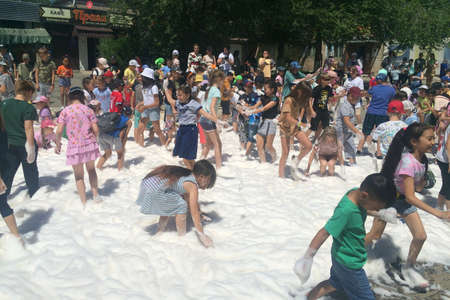 Orenburg, Russia - June 18, 2021, Children play in the foam. Soap show on the street Editorial.