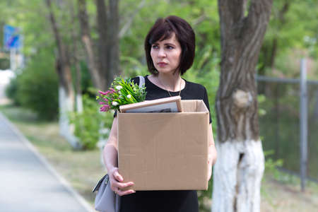 Upset brunette manager after being fired with box of personal belongings is walking down the street.