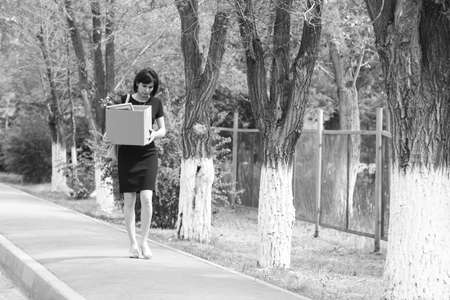 Upset brunette manager after being fired with a box of personal belongings is walking down the street. Black and white