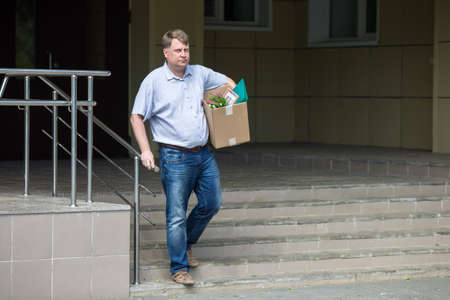 A sales manager leaves the office after being fired with a box of personal belongings.