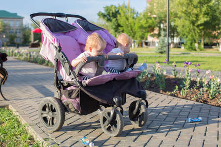 An unattended stroller with two children in city park.