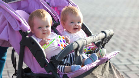 Smiling twin girls in baby carriage with bright toys in their hand.