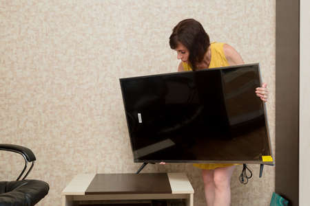 A woman installs a new TV on a table in the apartment.