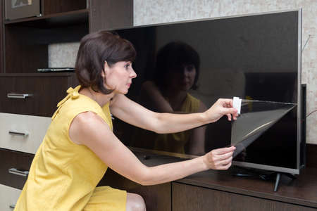 An adult brunette woman with rainbow removes a protective film from a new lcd TV screen.