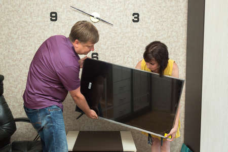 A man and a woman bring new TV into the apartment.