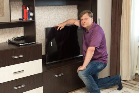 An adult man puts a new large TV in place.