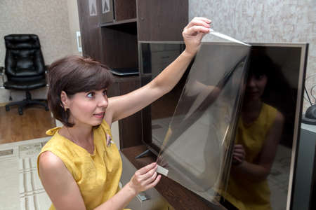 An adult brunette woman with a rainbow removes a protective film from a new lcd TV screen. 版權商用圖片