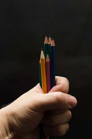 Several colored pencils in a man's fist on a gray background.