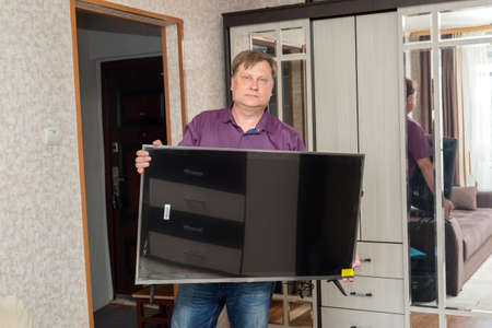 An adult blonde man brings a new large TV into the room.