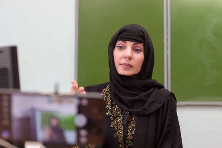 A Muslim teacher conducts a lesson remotely in a school classroom during a pandemic.