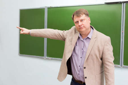 A strict teacher shows the student the exit to the door from the classroom with a hand gesture. 版權商用圖片