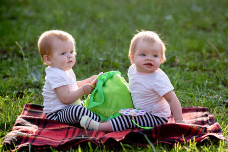 Two twin children on a blanket in park play with a children's backpack.