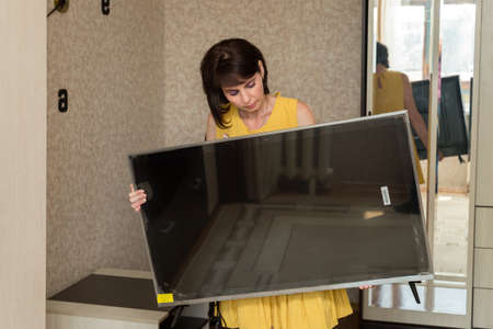 A brunette woman in a yellow dress brings a new large LCD TV into the apartment. 版權商用圖片