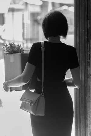 A fired brunette in a black dress with a box of personal belongings. Black and white