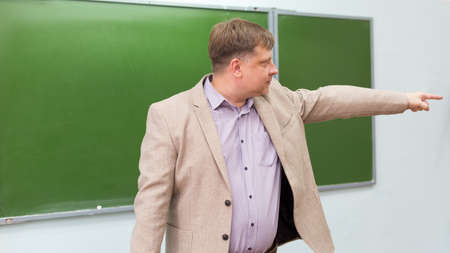 A strict teacher shows the student the exit to door from the classroom with a hand gesture.