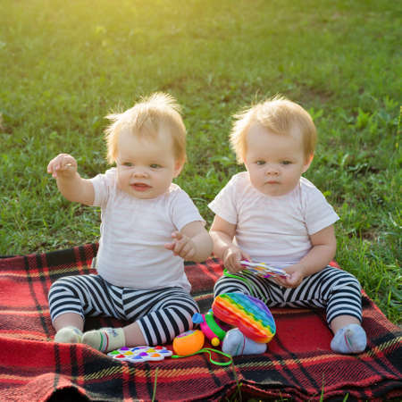 Twin girls play with bright toys on blanket in a city park.
