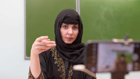 A Muslim teacher conducts a lesson remotely in school classroom during a pandemic.