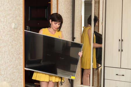 A brunette woman in yellow dress brings a new large LCD TV into the apartment.