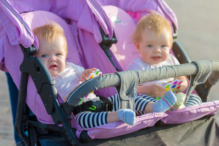 Two twin sisters are sitting next each other in a baby stroller with toys in their hands.